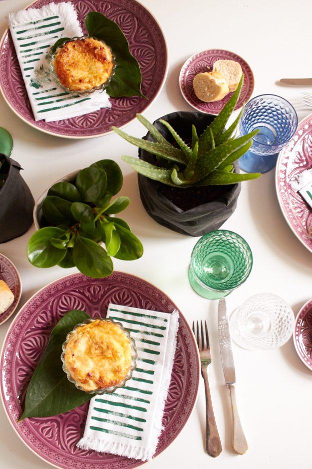 Ein schön gedeckter Tisch mit viel Grün im Pflanzen-Look.